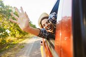 Image of gorgeous woman 20s wearing straw hat laughing and waving hand out of the window while ridin poster