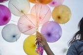 Beautiful Woman Holding Balloons, Colorful Of Multicolored Balloons Floating In The Sky. poster