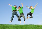 stock photo of triplets  - happy smiling group of kidschildren boys jumping for joy - JPG