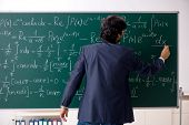 Young male math teacher in classroom  poster