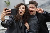 Image of satisfied couple man and woman 20s in warm clothes taking selfie photo on cell phone while  poster