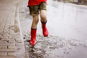 Child Wearing Red Rain Boots Jumping Into A Puddle. Close Up. Kid Having Fun With Splashing With Wat poster