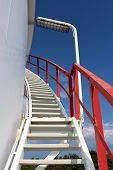 Spiral Metal Stairs Mounted On Side Of Large Storage Silo With Red Security Fence And Large Light On poster