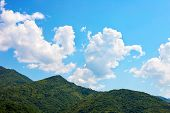 Incredible Bright Seascape. View Of Green Wooded Mountains And Blue Sea, Blue Sky And White Clouds.  poster