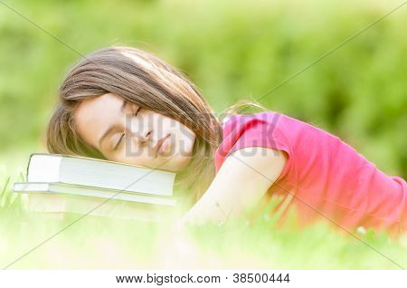 Young Student Girl Sleeping On Pile Of Books