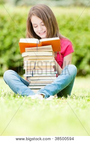 Happy Student Girl Sitting On Grass And Reading