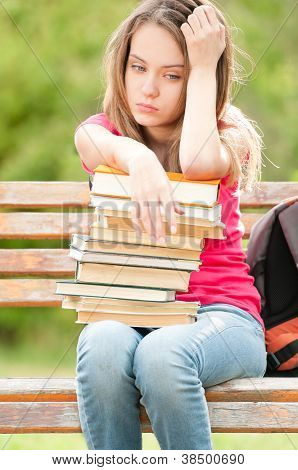 Sad Young Student Girl Sitting On Bench With Books