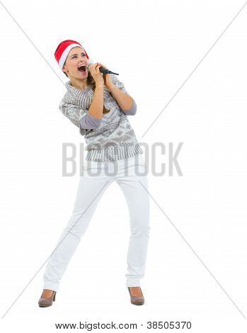 Happy Woman In Santa Hat Singing In Microphone And Looking On Co