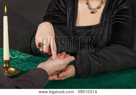 A Dark Dressed Woman Is Doing A Palm Reading