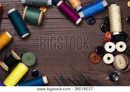 Threads Buttons And Needles On The Brown Wooden Table