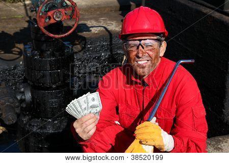 Trabalhador satisfeito segurando o dinheiro no campo de petróleo