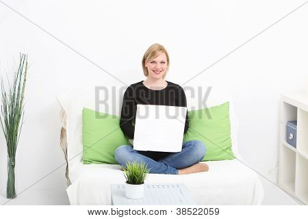 Attractive Blonde Woman Sits On Sofa