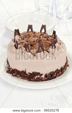 Chocolate cake with pile of plates