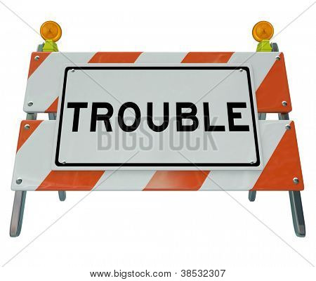 The word Trouble on a construction barrier or barricade to warn caution that there is a problem, danger ahead or other issue or mess