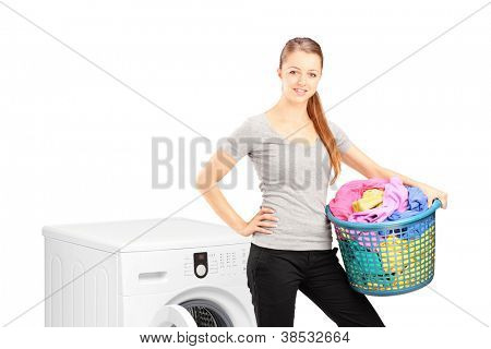 A smiling woman with laundry basket posing next to a washing machine isolated on white background
