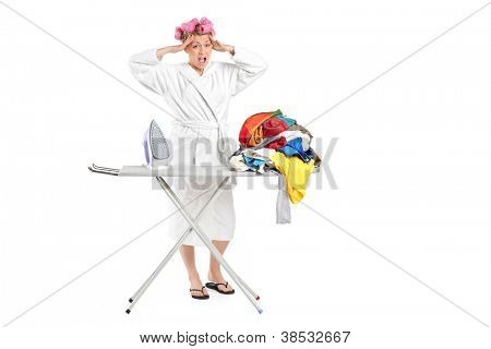 Annoyed housewife with ironing board and clothes isolated on white background