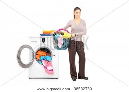 Full length portrait of a smiling woman holding a laundry basket next to a washing machine isolated on white