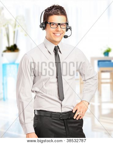Handsome male customer service operator with headset posing in his office
