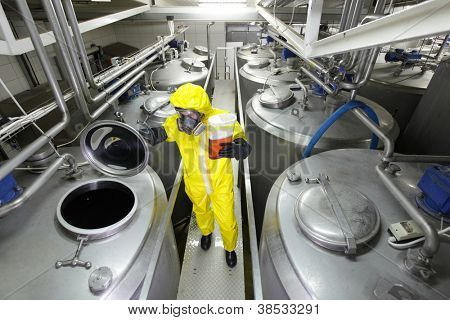 industrial professional with sample in container, in protective uniform,mask,goggle s,gloves and wellies controlling industrial process