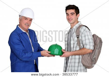 young apprentice and  mature workmate in jumpsuit