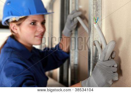 Tradeswoman installing electrical wiring