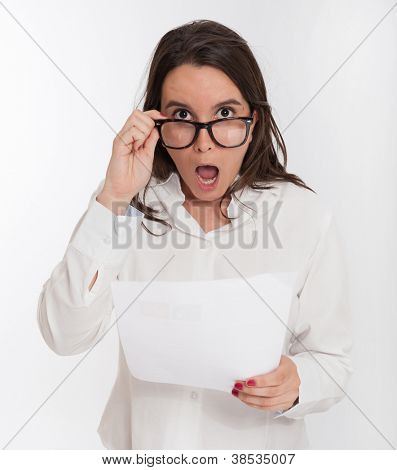 Young brunette looking shocked to a document