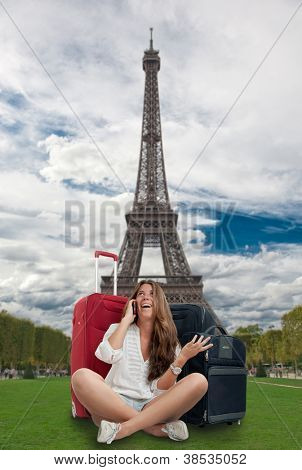 Happy girl on the phone with her baggage by the Eiffel Tower