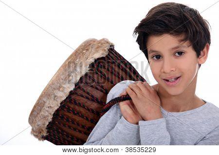 Little boy carrying bongo over shoulder