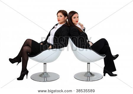 Two businesswomen sat in designer chairs