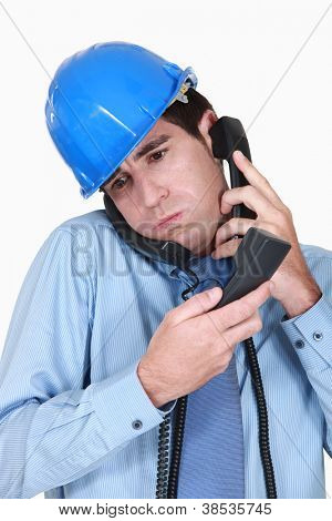 Overwhelmed engineer answering ringing phones