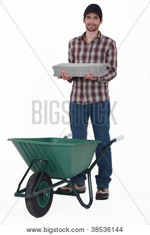 Mason placing brick in wheelbarrow