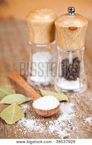 sal e pimenta em colher e shakers, folhas de louro na mesa de madeira rústica