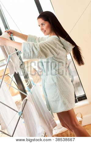 Beautiful woman hanging freshly washed clothes on the rack