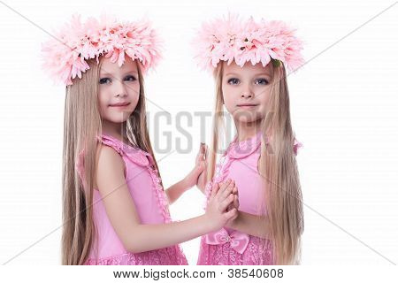Two beautiful little girls in pink dresses