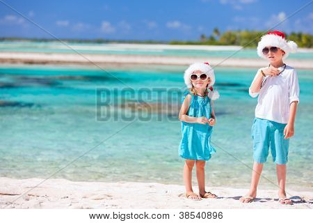 Boy and girl wearing Santa hats at tropical beach