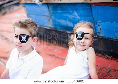 Cute little pirates boy and girl sitting at old boat