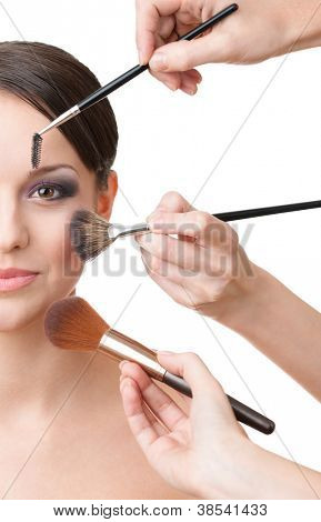 Three hands of makeup artists applying cosmetics on the woman's face, isolated on white. Half face shot