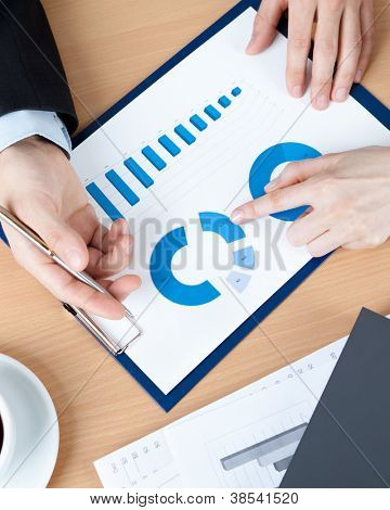 Top view of hands of business people at the table with documents