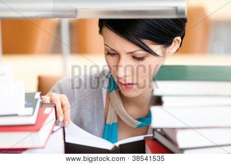 Reading book female student sitting at the desk surrounded with piles of books at the library. Information concept
