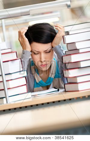 Tired beautiful woman with headache sitting at the desk surrounded with piles of books