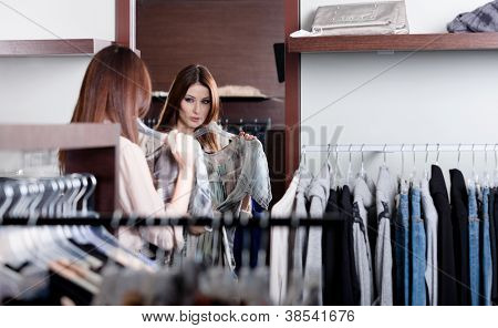 Woman admires herself at the mirror in the shopping mall