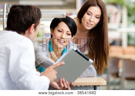 Man sitting at the table at the library shows something interesting in the tablet to two women