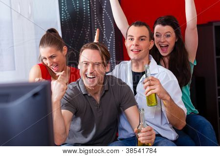 Two couples watching sports in the telly, they all are really excited, drink beer and cheer their team