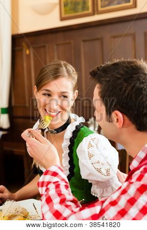 Young people in traditional Bavarian Tracht eating in restaurant or pub lunch or dinner, focus on salad in the foreground