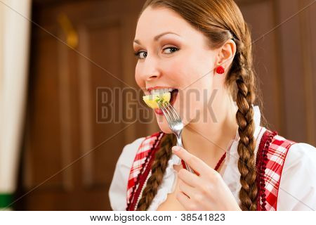Young woman in traditional Bavarian Tracht eats in restaurant potatoes