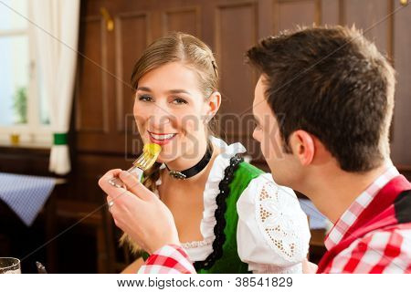 Young couple in traditional Bavarian Tracht eating in restaurant or pub lunch or dinner
