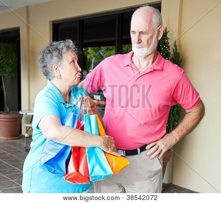 Senior woman addicted to shopping looks guilty as she explains to her husband.