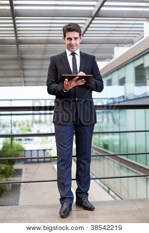 Smiling young businessman using his digital tablet at the office