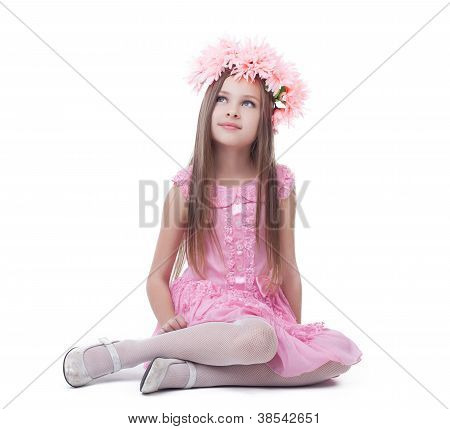 Little girl in pink dress and wreath sitting