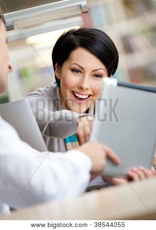 Woman communicates with man showing her something in the pad sitting at the table at the library
